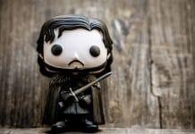Game of Thrones - Boneco de Jon Snow, da série Funko! Pop, com uma superfície de madeira ao fundo.