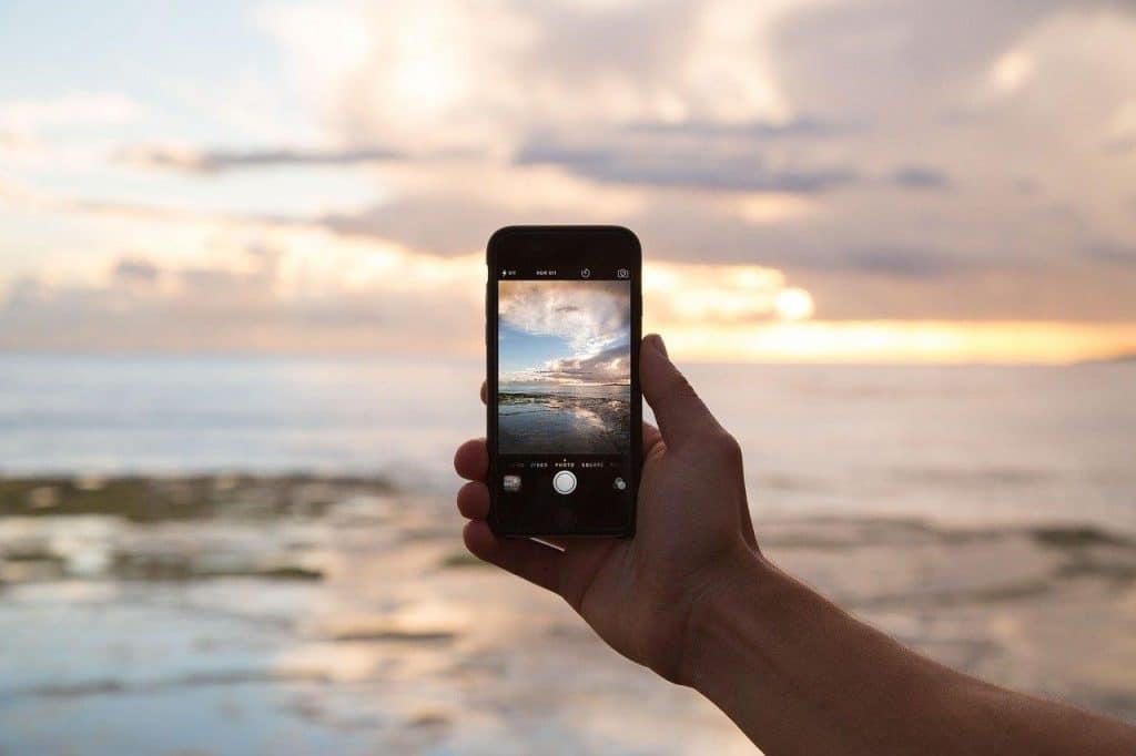 Segurando o celular e filmando pôr do sol
